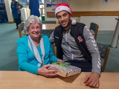 Rudy Gestede presents Gerry Knowles with a MFC Christmas gift