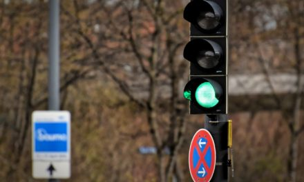 What should you do if you encounter a faulty traffic light?
