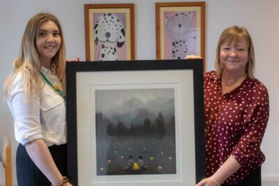 The print will join other examples of Mackenzie Thorpe's work on display in the hospice. Pictured: fundraiser Emily Robson and family support team leader Deborah Robinson