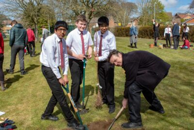IT Technician Jake Smith (right) stepped away from the computer to help Amam Agarwal, William Nichols, and Harsimran Singh plant their tree